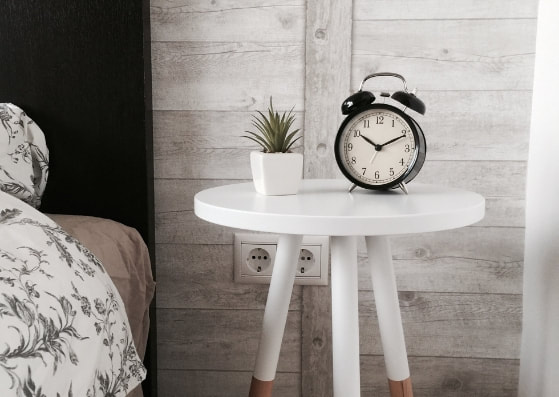 black alarm clock and succulent on white bedside table