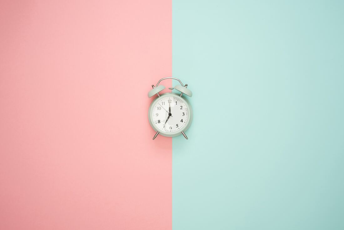 alarm clock on striped pink and teal background