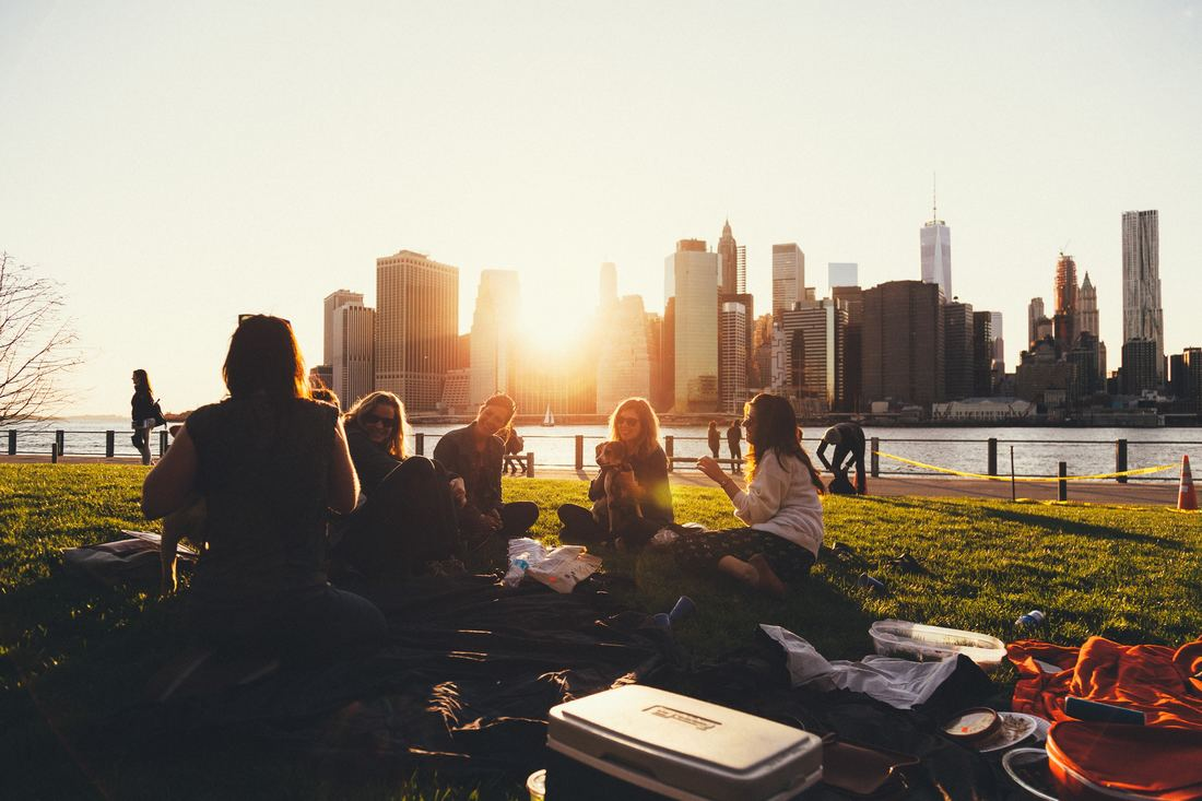 a group of friends having a picnic at sunset with city skyline in background