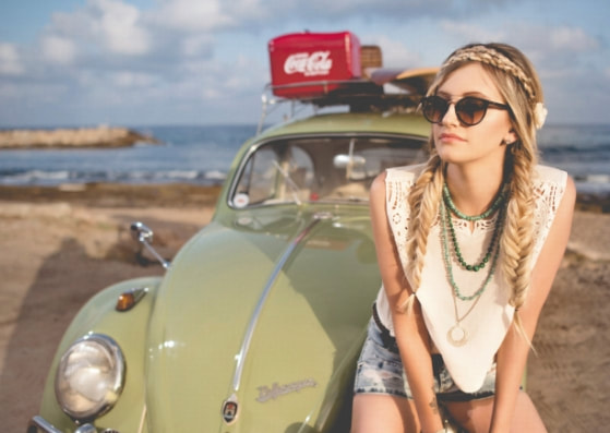 boho girl in sunglasses sitting on the hood of a green beetle on the beach