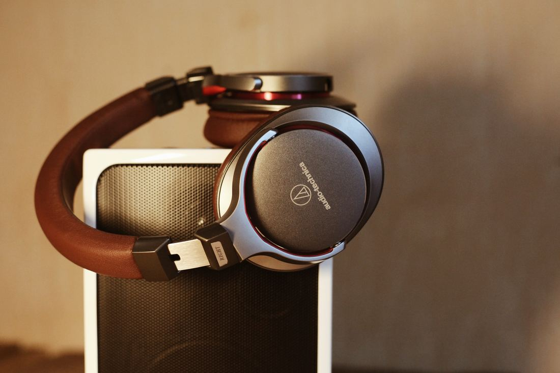 brown headphones on silver speaker