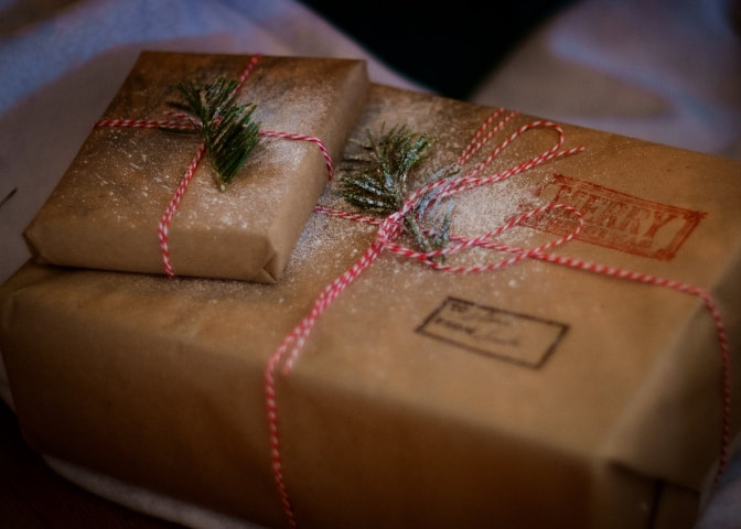 Christmas presents wrapped in brown paper and red string