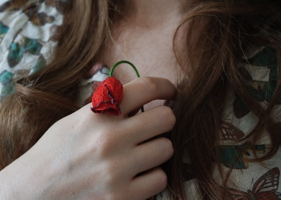 closeup of girl holding a withered rose to her heart
