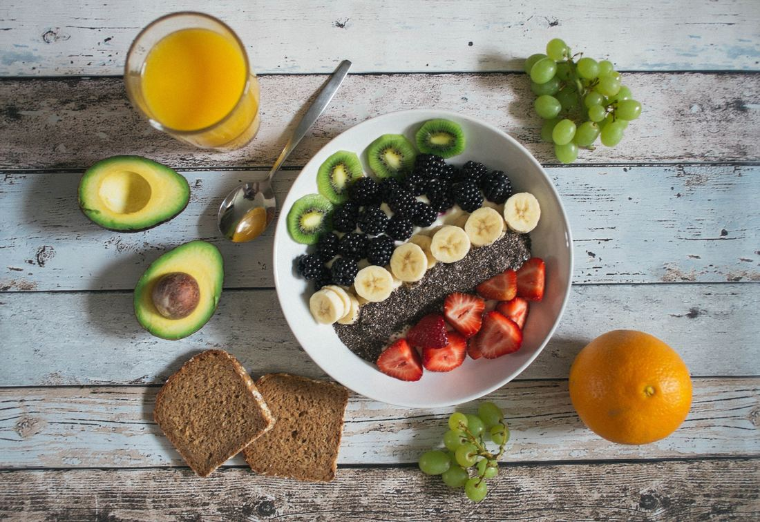bowl of fruits and berries on wooden background surrounded by avocado, toast, and orange juice