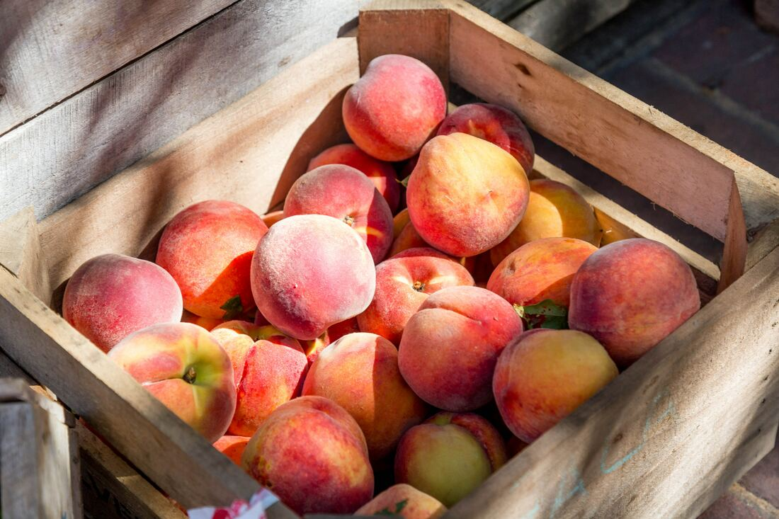 wooden crate full of peaches in the sunlight