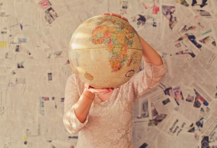 woman holding a globe in front of her face with newspaper covered wall in background