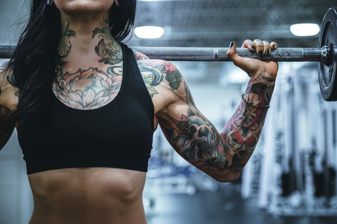fit woman with tattoos and squat bar on her shoulders at the gym