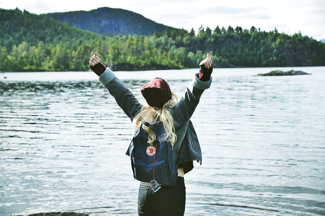 girl by a lake in a backpack in a winning pose