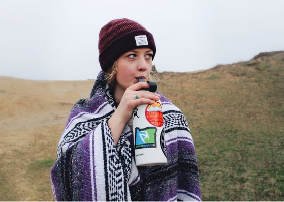 Girl in hat and Mexican blanket sipping water in the mountains