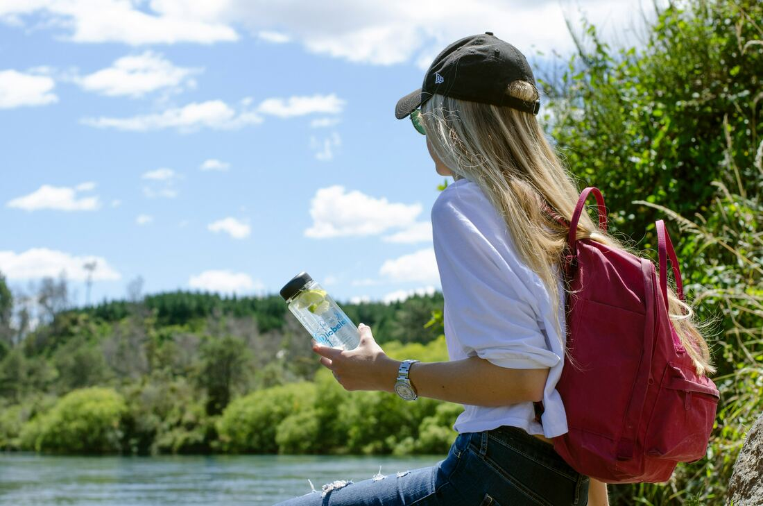 Girl in hat and red backpack holding a water bottle sitting by a lake