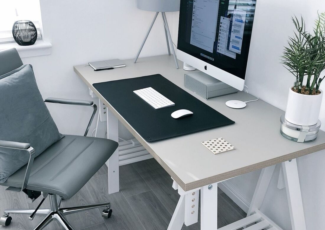 Gray office with desk, chair, monitor, and plant