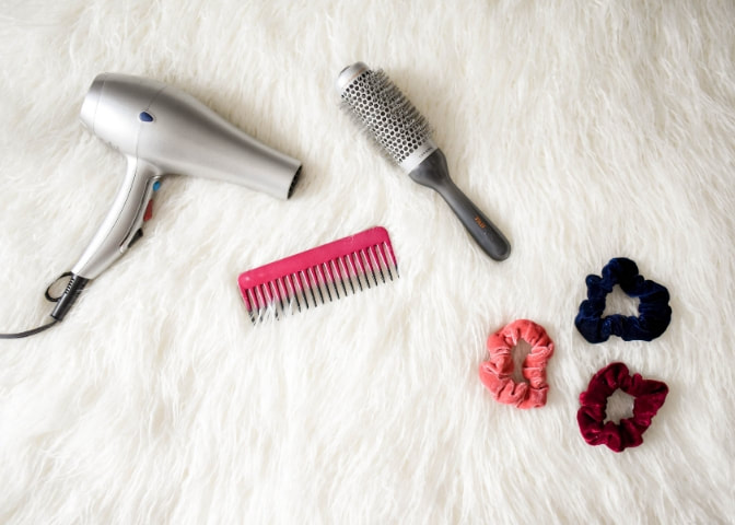 Hair dryer and styling tools on white faux fur