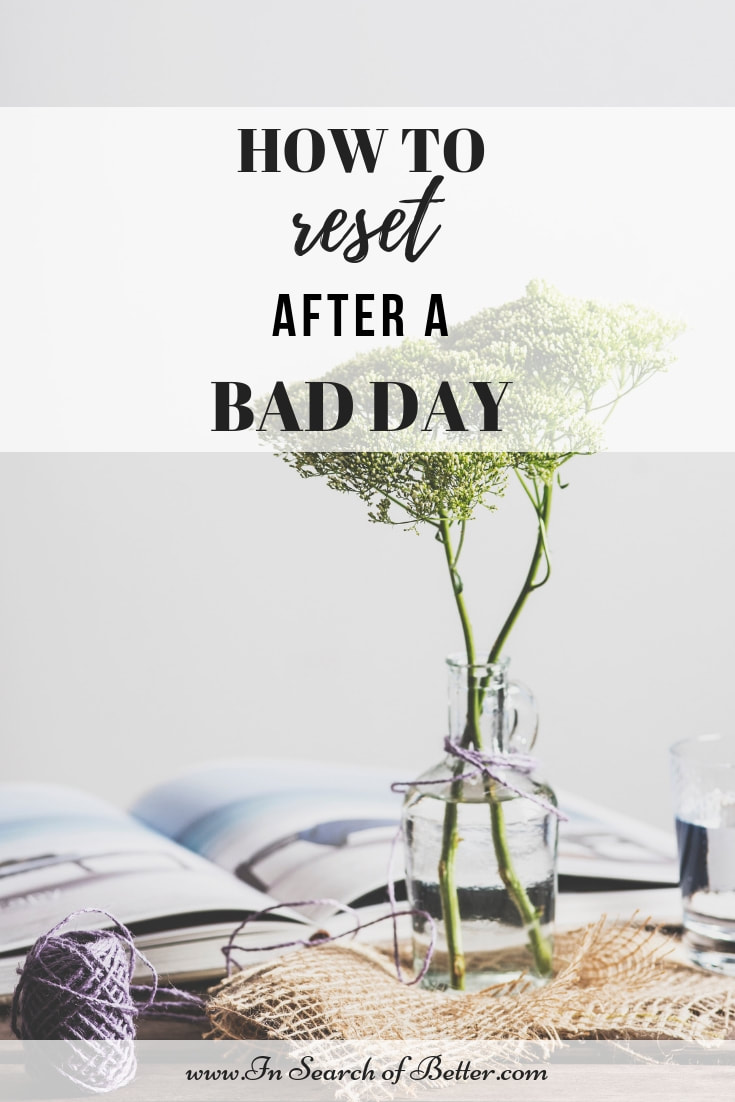 Flower in glass bottle on table with open book with text overlay - how to reset after a bad day