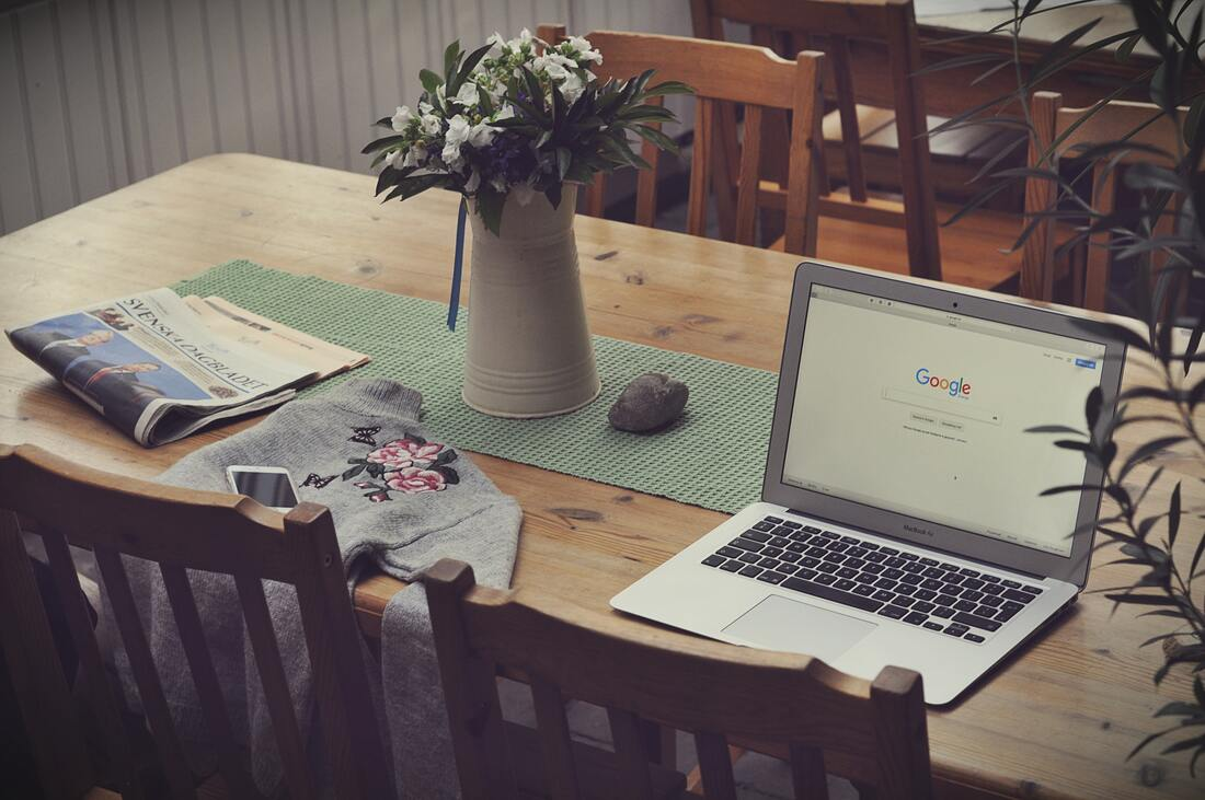 Open laptop on table with sweater, newspaper, and flower vase