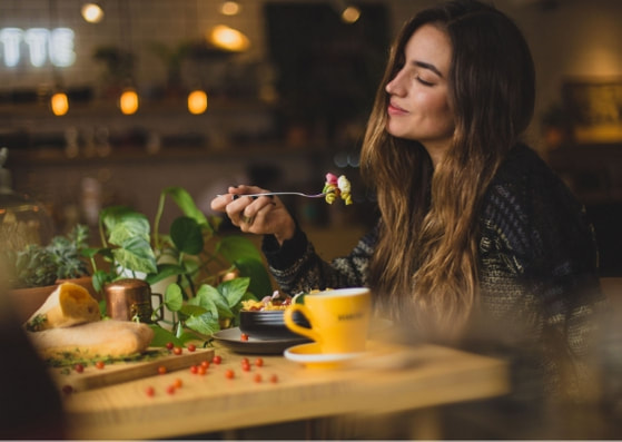 Woman eating alone in restaurant enjoying her food