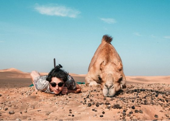Man and camel lying on desert ground facing the camera