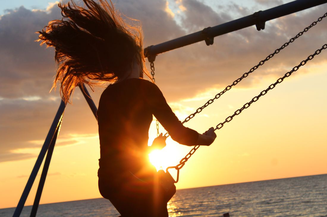 girl on swing at sunset