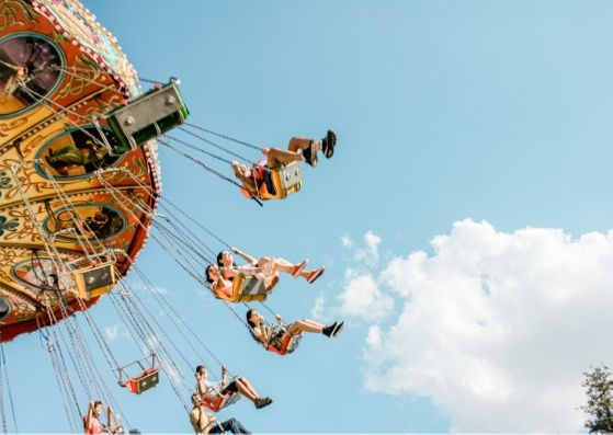 People riding a flying carousel against the blue sky