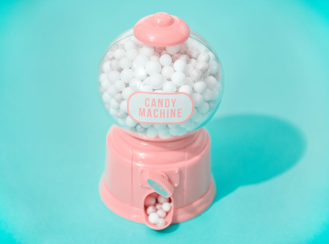 pink bubble gum machine with white candy on teal background