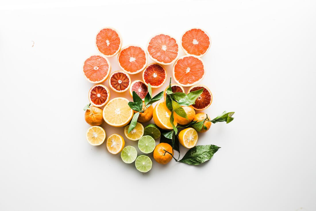 Slices of orange, lime, and blood orange on white/gray surface