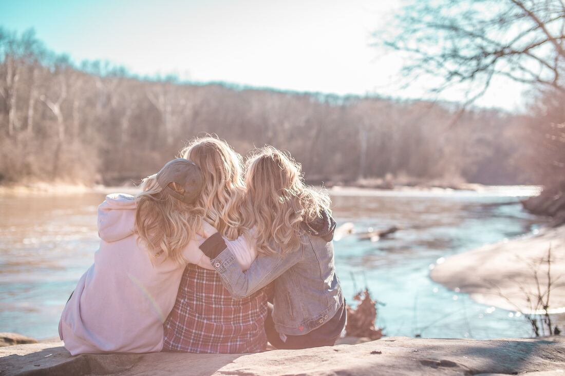 three girls hugging each other by creek
