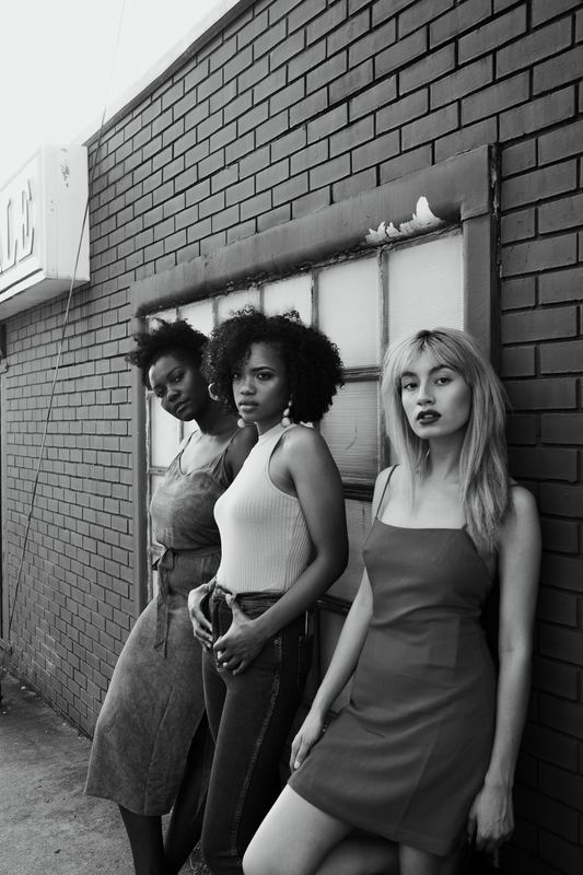 black and white photo of three girls leaning against a wall, looking confidently into the camera