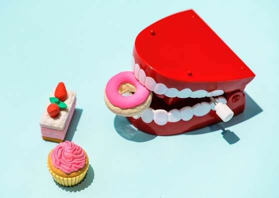toy dentures eating mini donut, with mini cupcake and cake slice on light blue background