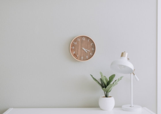 minimalistic desk with lamp, plant, and wooden clock on the wall
