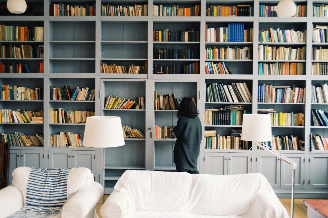 woman browsing shelves in a book store with white couches