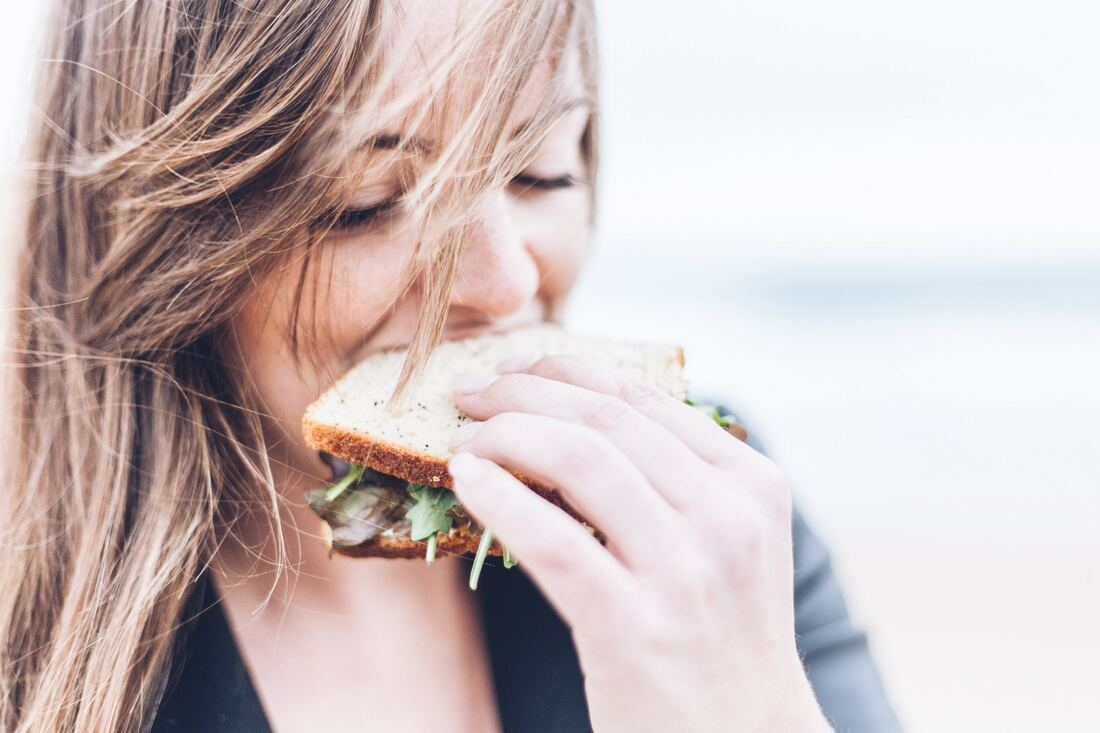 Woman eating a sandwich with greens