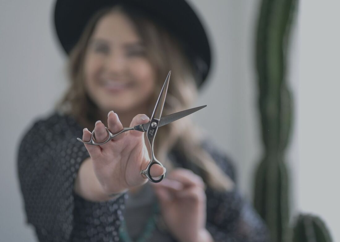 Woman in hat holding up scissors in front of her