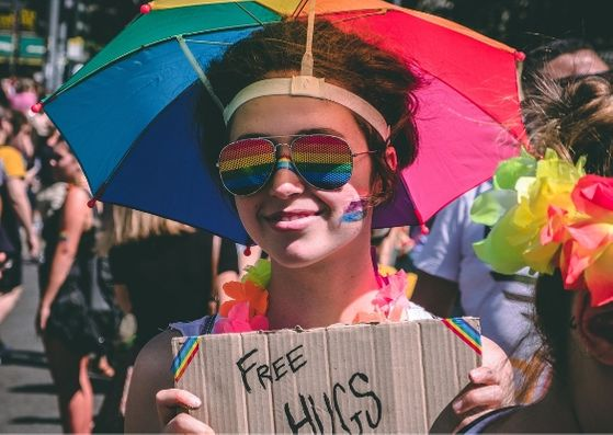 Woman in umbrella hat holding free hugs sign